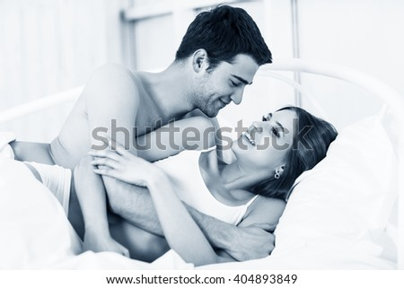 Loving couple in bed. - stock photo