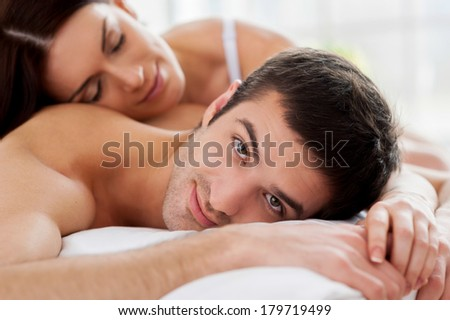 Loving couple in bed. Cheerful young loving couple lying in bed and smiling at camera - stock photo