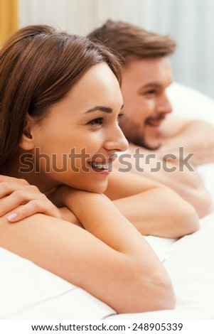 Loving couple in bed. Side view of beautiful young loving couple lying in bed together and smiling