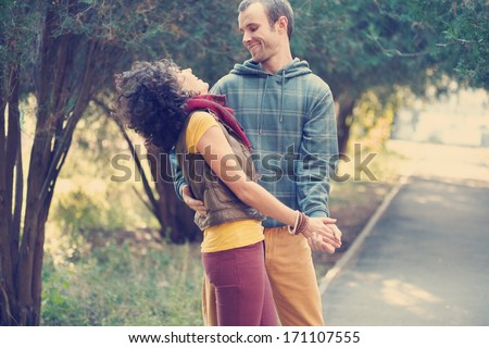 Loving couple in bright clothes dancing on the park alley - stock photo