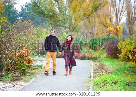 Loving couple in bright clothes walking along park alley holding hands - stock photo