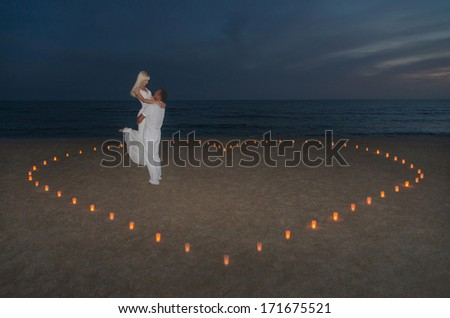 Loving couple in candles heart at sea beach against sunset- St.Valentines Day romantic concept - stock photo