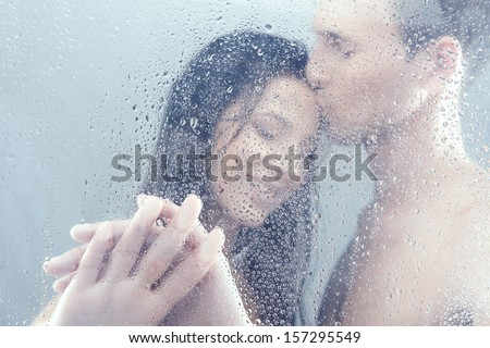 Loving couple in shower. Beautiful loving couple hugging while standing in shower
