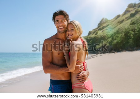 Loving couple in swimsuit embracing on the beach. Romantic young couple on sea shore  looking away and smiling.