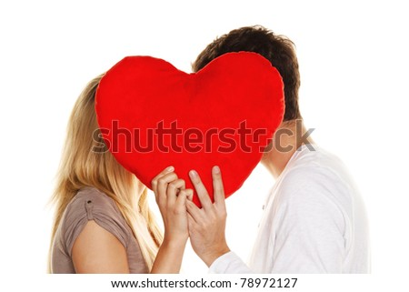 Loving couple kissing behind a heart. Love is beautiful. Secret love - stock photo