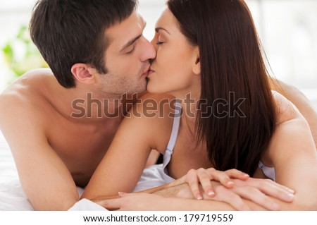 Loving couple kissing in bed. Beautiful young loving couple lying in bed and kissing - stock photo