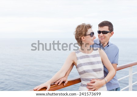 loving couple looking at each other and enjoying cruise together - stock photo