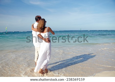 Loving couple looking the ocean. Romantic vacation. - stock photo