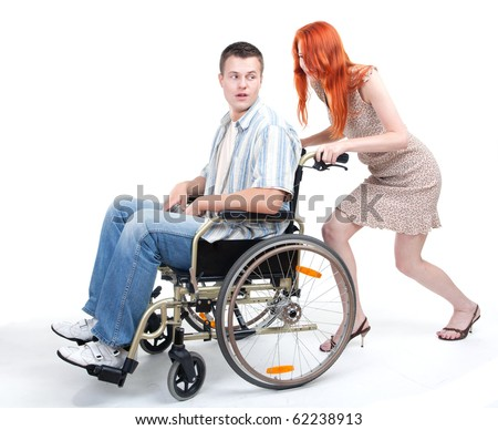 loving couple - man on wheelchair lead by woman - stock photo