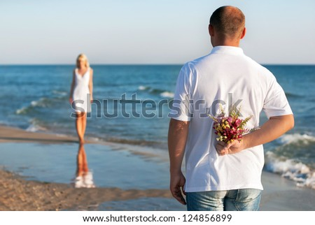 loving couple - man with flower bouquet waiting his woman on the sea beach at summer - the romantic dating or wedding or valentines day concept - stock photo