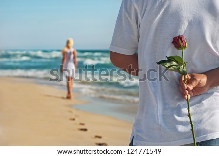 loving couple, man with rose waiting his woman on the sea beach at summer, the romantic, wedding or valentines day concept - stock photo