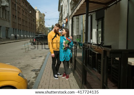 loving couple on a date, walking on a city street. The girl holding a bouquet of tulips. - stock photo