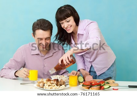 Loving couple on kitchen eating ketchup - stock photo