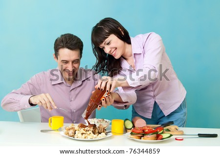 Loving couple on kitchen eating ketchup