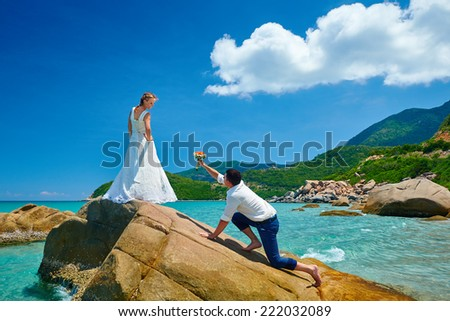 Loving couple on sea beach - a man making proposal with bouquet to his pretty woman in wedding dress