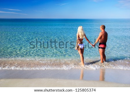 loving couple on the sea sand beach looking at the blue sky