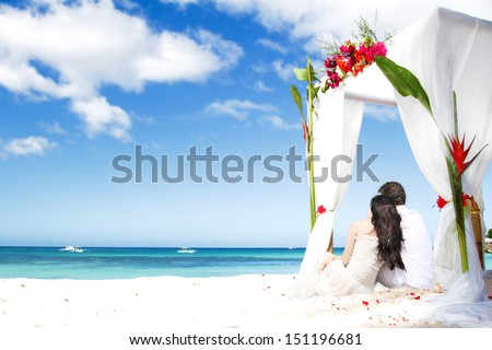 loving couple on wedding day near bamboo arch with flowers on tropical sea background - stock photo