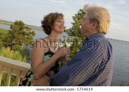 loving couple outside on a deck with wine glasses - stock photo