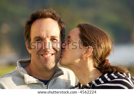 Loving couple outside, the wife is giving her husband a kiss on the cheek