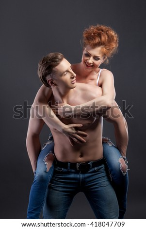 Loving couple posing in studio, on gray background