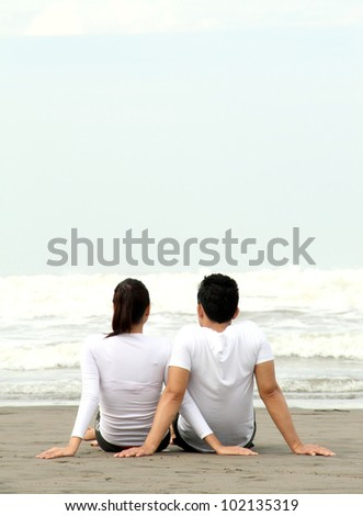 loving couple relaxing and spending quality time with each other on beach - stock photo