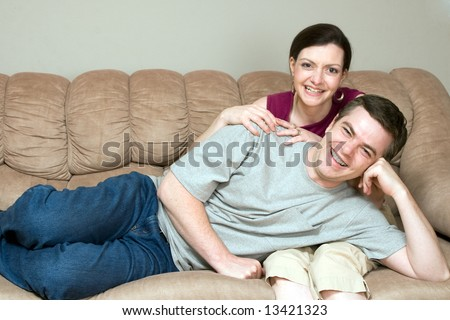 Loving couple relaxing on their couch together. He is lying on her lap. Both are looking at the camera with a smile on their faces. Horizontally framed shot. - stock photo