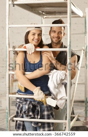 Loving couple renewing home, smiling happy, embracing under scaffold. - stock photo