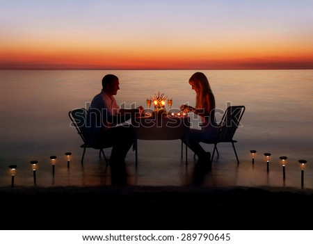 Loving couple share a romantic dinner with candles and lanterns light way at sea beach in water against wonderful sunset - stock photo