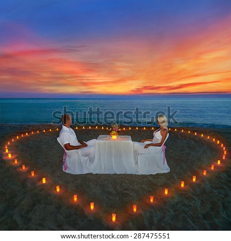 Loving couple share romantic dinner with candles heart at sea beach sand looking for wonderful sunset - stock photo
