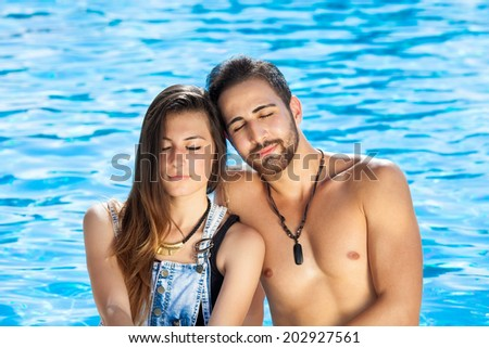 Loving couple sharing a quiet moment in front of a cool sparkling blue swimming pool resting their heads against each other with their eyes closed in meditation - stock photo