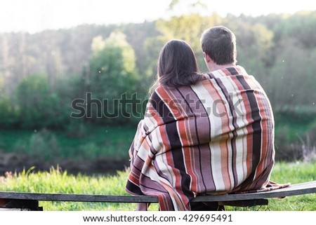 Loving couple sits on the bench over wonderful spring landscape - stock photo