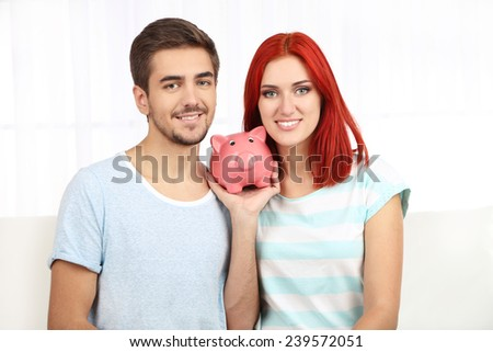 Loving couple sitting in sofa with piggy bank in room - stock photo