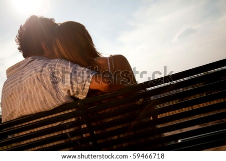 Loving couple sitting on a bench enjoying the sun - stock photo