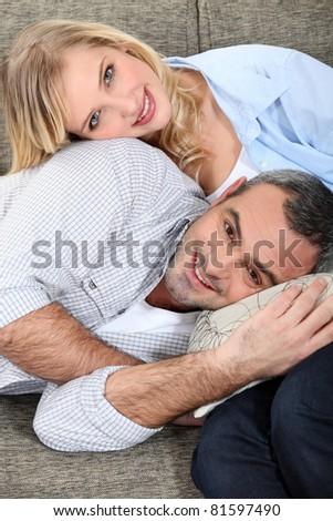 Loving couple sitting on a sofa - stock photo