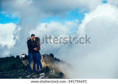 Loving couple sitting on mountain meadow and enjoying view of nature at sunny day in autumn.