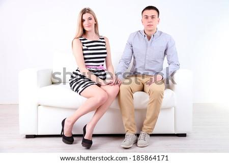 Loving couple sitting on sofa, on light background - stock photo