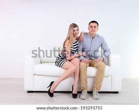 Loving couple sitting on sofa, on light background - stock photo