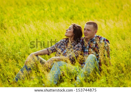 loving couple sitting on the grass in the field - stock photo