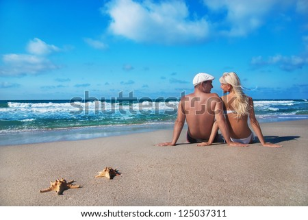 loving couple sitting on the sea sand beach and look at each other - stock photo
