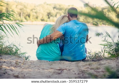 Loving couple spending leisure time together at beach sitting on sea shore with red heart hugging rear view - stock photo