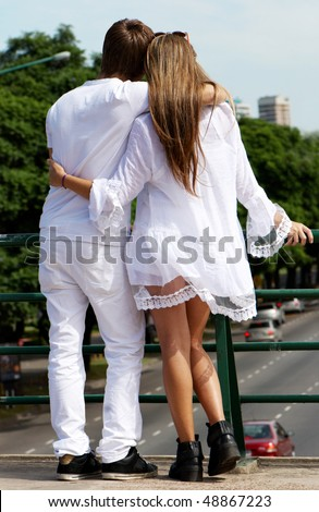 Loving couple standing and hugging against  in city. - stock photo