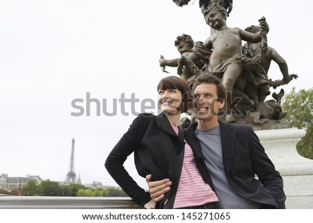 Loving couple standing in front of sculpture - stock photo