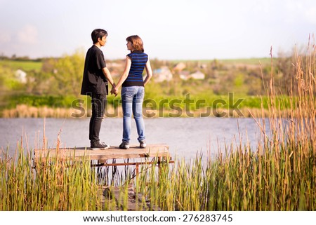 loving couple standing near the water on the pier - stock photo