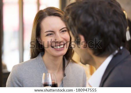 Loving couple takes a drink in restaurant, focus on woman