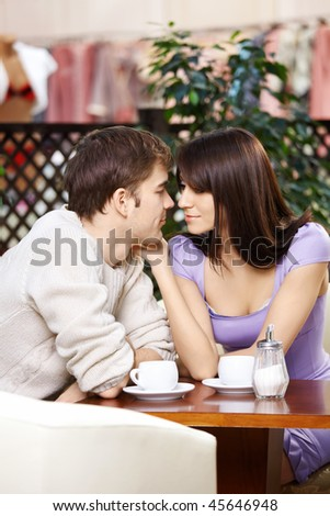 Loving couple talks behind a little table in cafe - stock photo