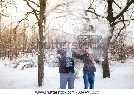 Loving couple throws snow in winter park. They put colored caps and scarves. Copy space. The girl hat with red hearts.