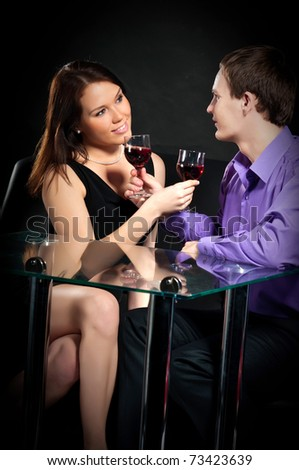 Loving couple toasting with wineglasses over a black background