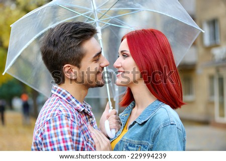 Loving couple under an umbrella in autumn park - stock photo