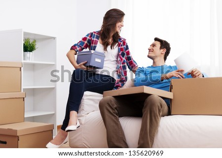 Loving couple unpacking in their new home - stock photo