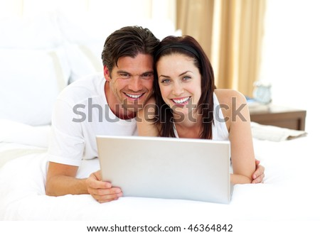 Loving couple using laptop lying on the bed - stock photo